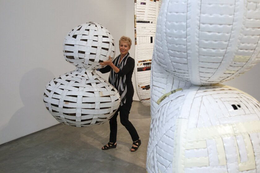 Artist Ann Weber carries one her sculptures made of cardboard at the Lux Art Institute, where she is the current Artist in Residence, in Encinitas.