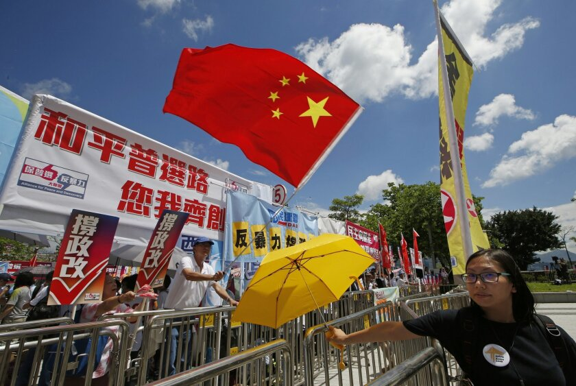 A pro-Beijing protester, left, holding a Chinese national flag confronts with a pro-democracy protester who is carrying a yellow umbrella outside the Legislative Council in Hong Kong, Wednesday, June 17, 2015. Hong Kong election reform proposals that sparked massive street protests last year in the