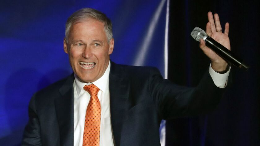 Democratic presidential candidate Washington Gov. Jay Inslee waves after speaking during a campaign