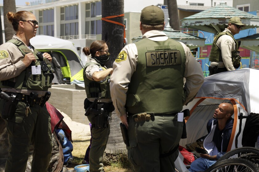 Sheriff's deputies approach a man living in a tent.