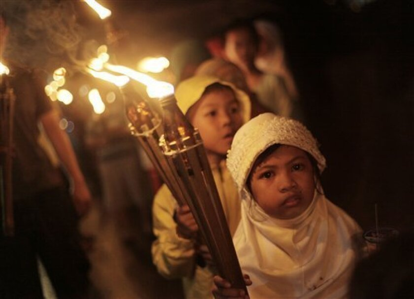 In this late Thursday, Sept. 9, 2010, an Indonesian Muslim girl carries a torch as she takes part in a parade celebrating Eid al Fitr prayer that marks the end of the holy fasting month of Ramadan at a neighborhood in Jakarta, Indonesia. Indonesia is the world's most populous Muslim country. (AP Photo/Dita Alangkara)