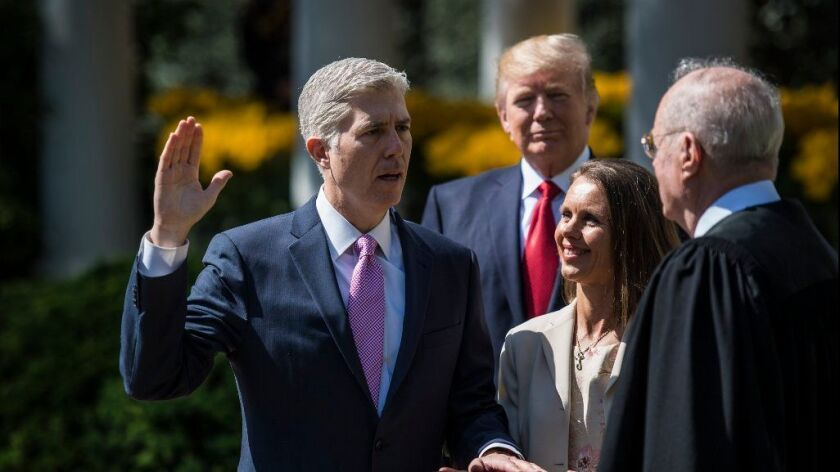 President Trump watches as Supreme Court Justice Anthony M. Kennedy administers the judicial oath to Neil M. Gorsuch in the White House Rose Garden on April 10, 2017.