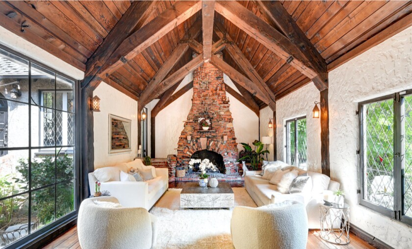 Built in 1927, the three-story home has lattice windows, dramatic beams and whimsical brick fireplaces.