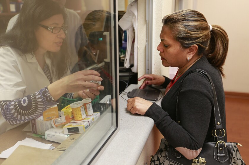 Lucia Jimenez has her prescription filled by pharmacist Alaria Kiraz, left, at AltaMed clinic in East Los Angeles.