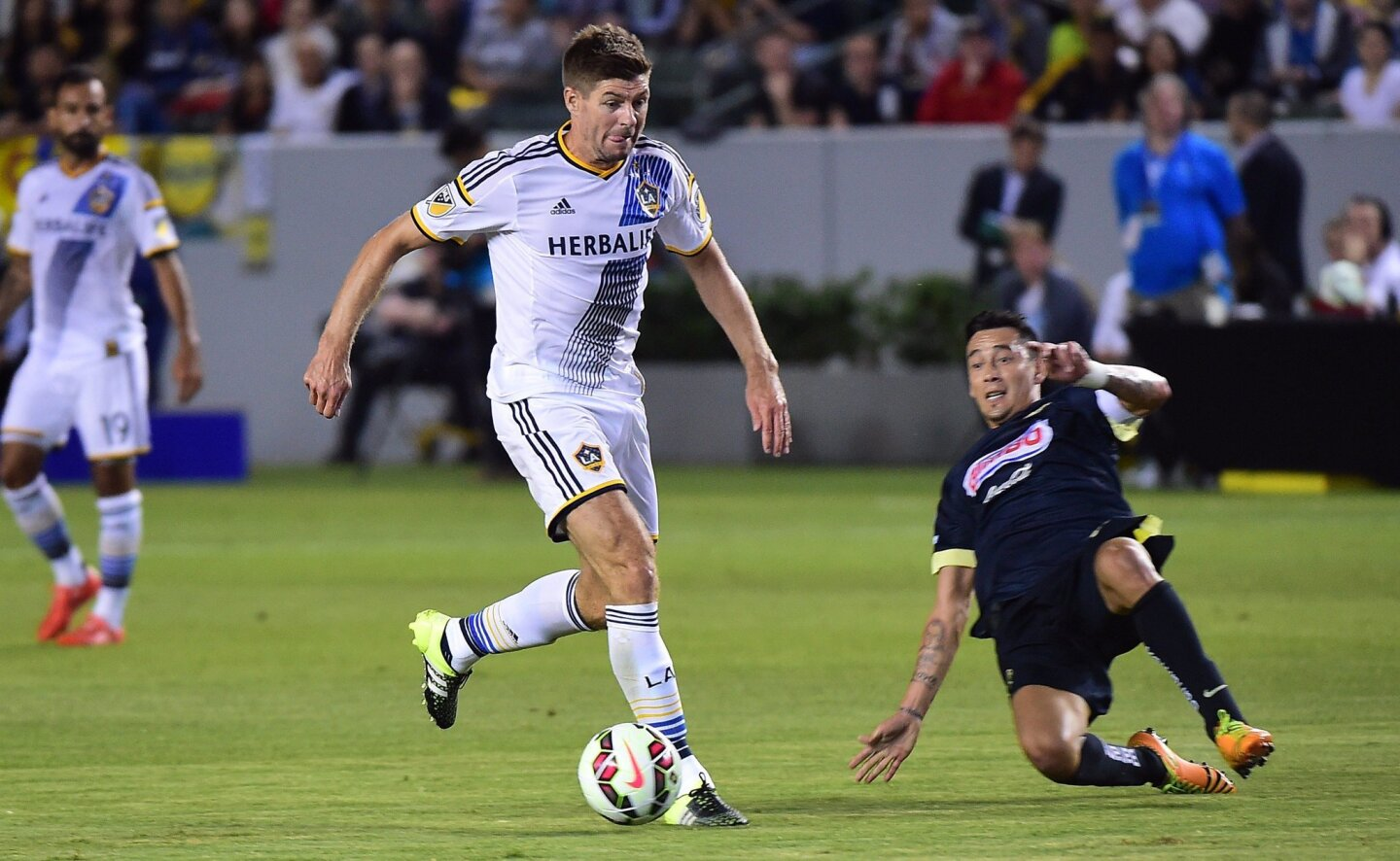 In his MLS debut, Liverpool FC legend Steven Gerrard (C) of the LA Galaxy looks to pass under pressure from Gil Buron of Club America on July 11, 2015 during their 2015 International Champions Cup match in Carson, California. AFP PHOTO / FREDERIC J. BROWNFREDERIC J. BROWN/AFP/Getty Images ** OUTS - ELSENT, FPG - OUTS * NM, PH, VA if sourced by CT, LA or MoD **
