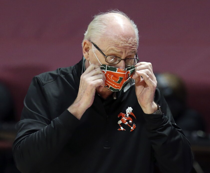 FILE - Miami head coach Jim Larranaga adjusts his mask during the first half of an NCAA college basketball game against Virginia Tech in Blacksburg, W.Va., in this Tuesday, Dec. 29, 2020, file photo. To move ahead of John Wooden on the list of coaching victories, Miami Hurricanes coach Jim Larranaga needs one win, which has been the case for three weeks. W's don't come easily, even for a coach with 664 of them. The Hurricanes are 4-5, their worst start in Larranaga's 11 seasons at Miami — and in fact their worst since 1992-93. (Matt Gentry/The Roanoke Times via AP, Pool, File)