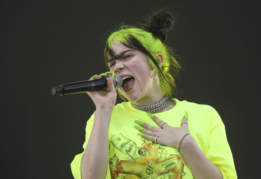 Billie Eilish, with florescent green hair and nails, sings into a microphone.