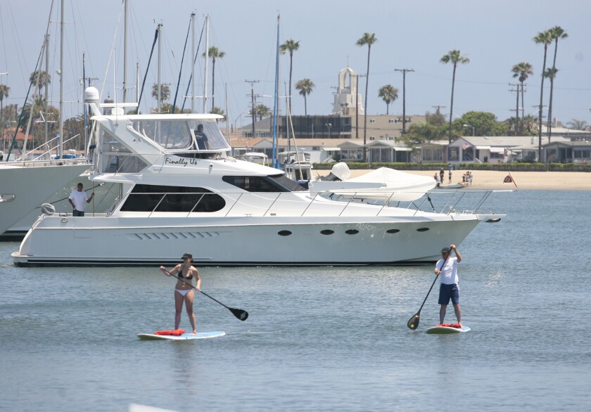 A pair of stand-up paddlers move past a pleasure boat out for an afternoon cruise in Newport Harbor.