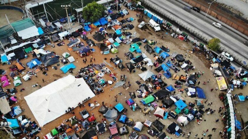 """An aerial view of the temporary shelter set up for members of the """"migrant caravan,"""" with a section of the U.S.-Mexico border visible, in Tijuana on Nov. 24."""
