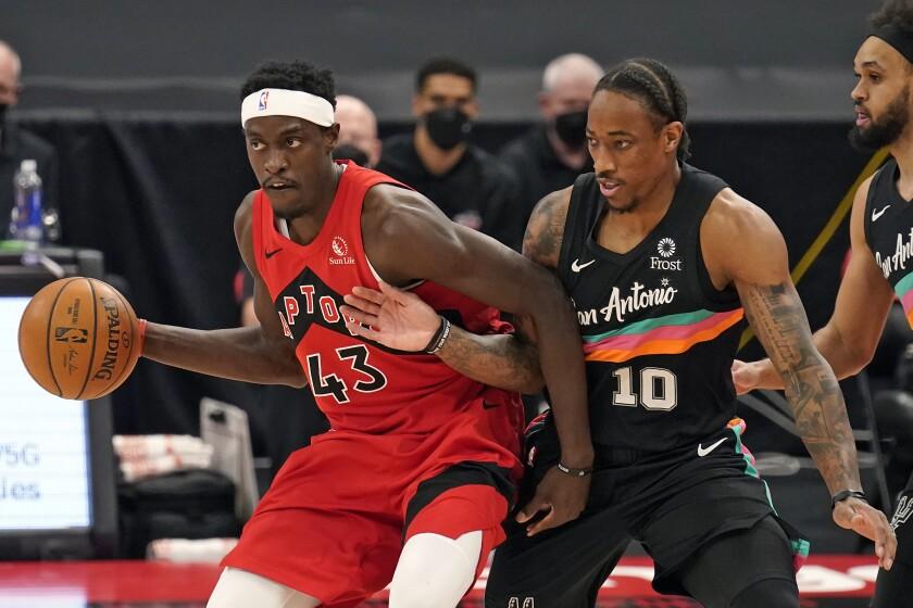 El alero de los Raptors de Toronto Pascal Siakam avanza con el balón mientras lo defiende DeMar DeRozan de los Spurs de San Antonio el miércoles 14 de abril del 2021. (AP Photo/Chris O'Meara)