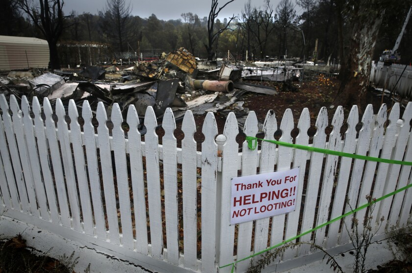 A sign on a fence in a Middletown neighborhood addresses the recent looting of homes that have been evacuated in the wake of the Valley fire.