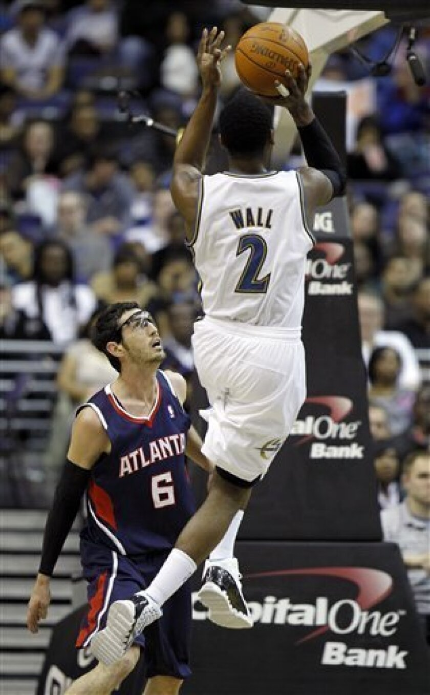 Atlanta Hawks guard Kirk Hinrich (6) watches as Washington Wizards guard John Wall goes up for a shot in the first half of an NBA basketball game Saturday, April 9, 2011, in Washington. (AP Photo/Alex Brandon)