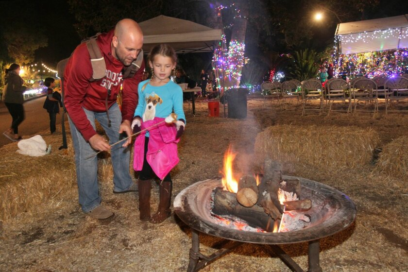 Brian Rowe and hs daughter Isla, 6, roast marshmallows at San Diego Botanic Garden's annual holiday Garden of Lights.