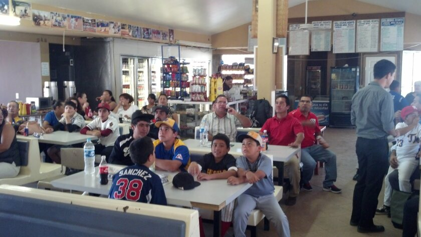 Locals watch the Tijuana Little League team from the cafeteria of Municipal de Tijuana Little League.