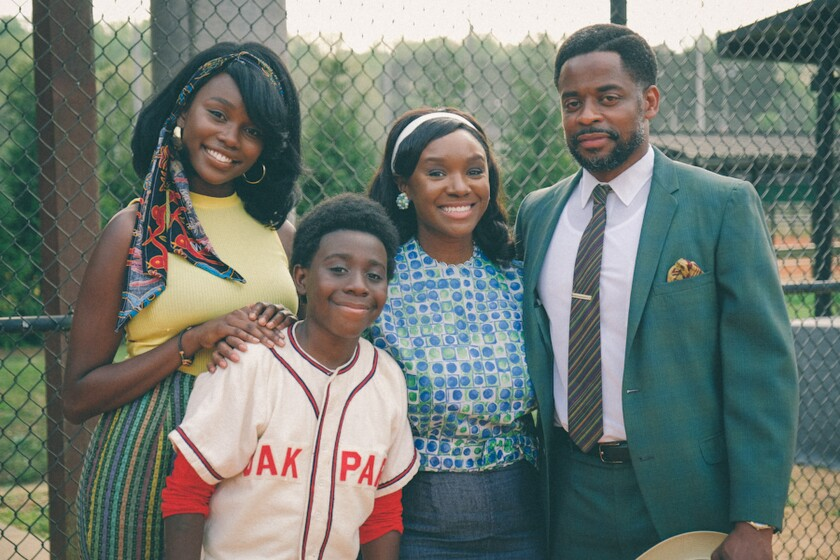 A Black family poses by a ball field in 1960s Alabama.