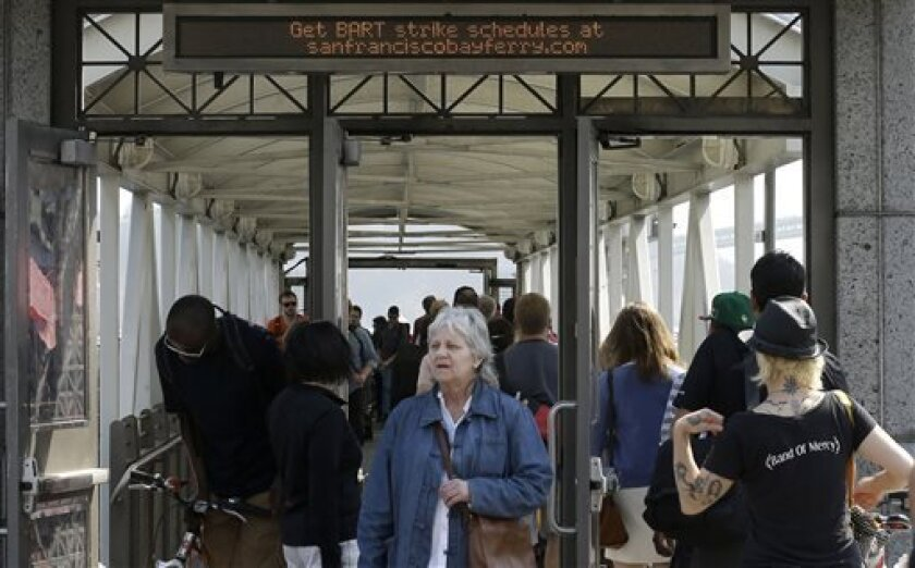 Commuters board a San Francisco Bay Ferry leaving for Oakland as passengers arrive from a ferry from Alameda at the Ferry Terminal in San Francisco, Tuesday, July 2, 2013. San Francisco Bay area commuters endured another tough morning commute on Tuesday, as a strike by workers for a heavily used train system entered its second day. Lines for ferries and buses appeared even longer than on Monday, and BART said charter buses it was running at four stations reached capacity before 7 a.m. and could