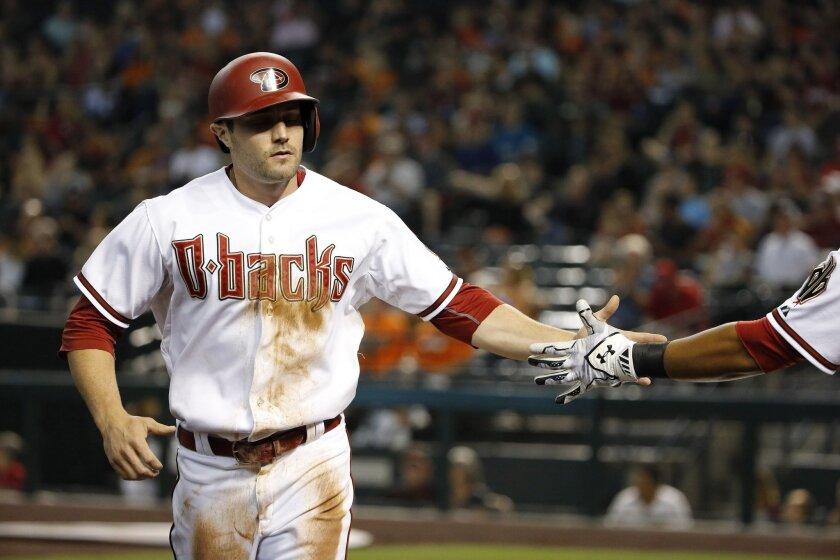 Arizona Diamondbacks' A.J. Pollock shakes hands with teammate Yasmany Tomas after Pollock scored a run against the San Francisco Giants during the first inning of a baseball game Friday, July 17, 2015, in Phoenix. (AP Photo/Ross D. Franklin)