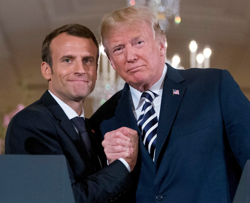 Presidents Emmanuel Macron of France, left, and Donald Trump stand side by side, hands clasped.