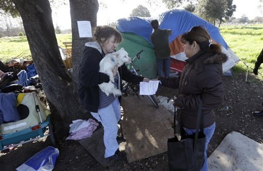 Wendy Clarke, left, holds her neighbor's dog Hero as she is handed an eviction notice by San Jose city worker Rita Tabaldo as city worker Mark Ruffing, center, attaches a notice to a Clarke's tent at a tent city in San Jose, Calif., Tuesday, March 5, 2013. The Silicon Valley is adding jobs faster t