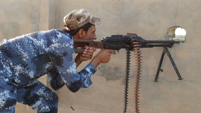 An Iraqi federal policeman fights the Islamic State group from the front line in eastern Husaybah, five miles east of Ramadi, Iraq, on June 4, 2015.