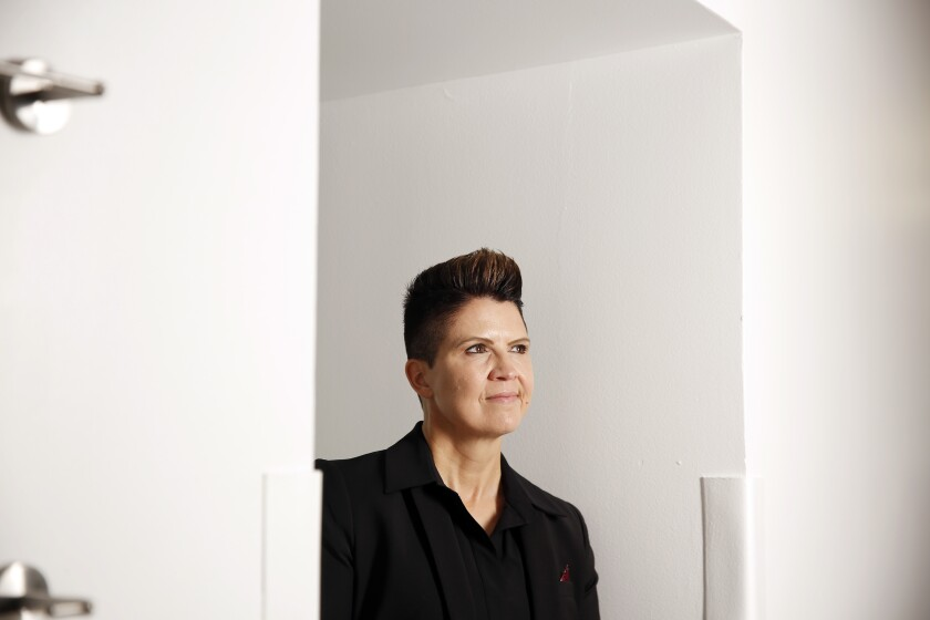 A woman wearing a dark top and jacket stands in an alcove between two white walls.