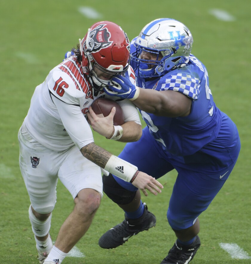 Kentucky defensive tackle Phil Hoskins (92) tackles North Carolina State quarterback Bailey Hockman (16) during a late fourth-quarter scramble in an NCAA college football game in Jacksonville, Fla., Saturday, Jan. 2, 2021. (Bob Self/The Florida Times-Union via AP)on via AP)