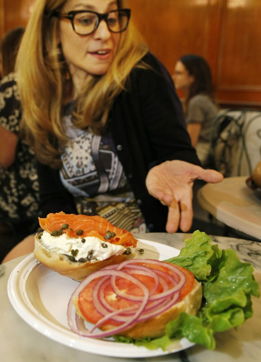 Ess-a-Bagel chief operating officer Melanie Frost discusses the finer points of a traditional bagel sandwich smeared with cream cheese, smoked salmon, red onion, lettuce, tomato, and capers at her family's midtown Manhattan bagel store, Thursday, May 26, 2016, in New York. Frost's late aunt, teache