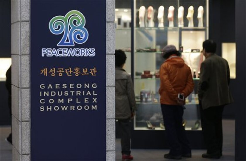 Visitors look at products made at Kaesong industrial complex in North Korea displayed at the complex's showroom at the unification observation post near the border village of Panmunjom, that has separated the two Koreas since the Korean War, in Paju, north of Seoul, South Korea, Thursday, April 18,