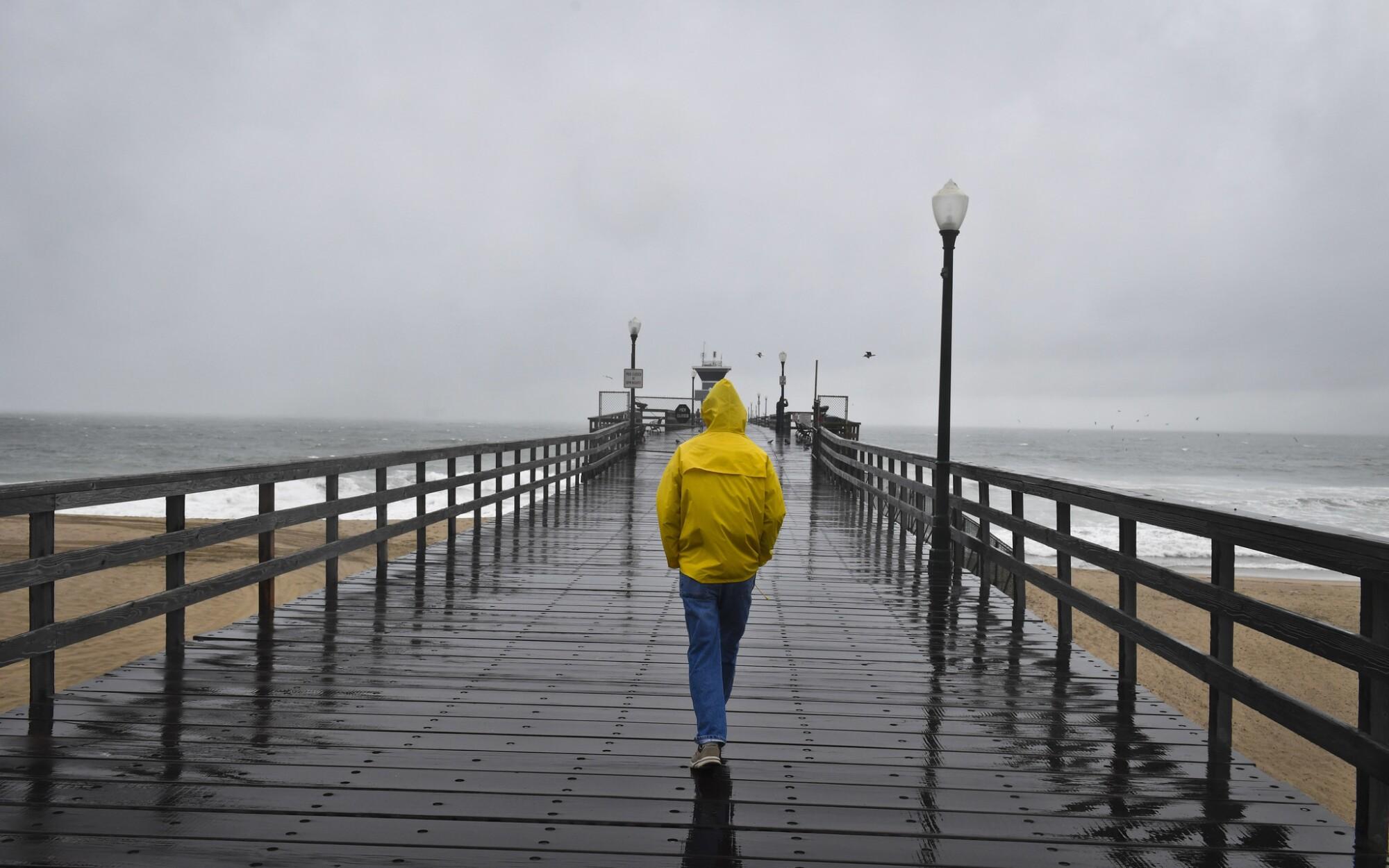 A pedestrian walks along Seal Beach Pier in the rain.