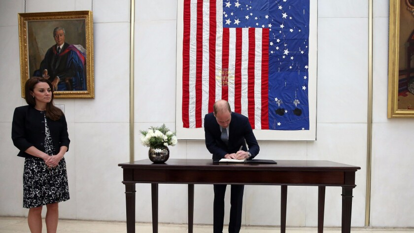 Britain's Prince William signs a book of condolence for the Orlando, Fla., nightclub shooting victims at the U.S. Embassy in London with Kate, duchess of Cambridge.