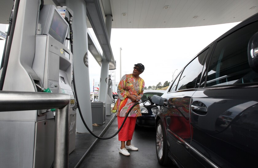 Eloise Ferguson of Ladera Heights pumps gas at a United Oil station at the intersection of Slauson and La Brea avenues in 2012.