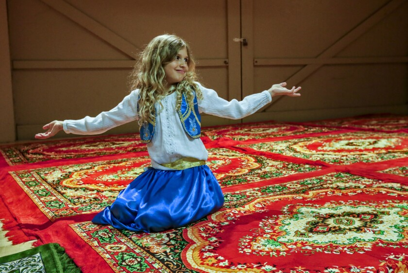 Jennah DiMartino, 7, plays on the rugs laid down for prayers at the community hall for prayers after iftar.