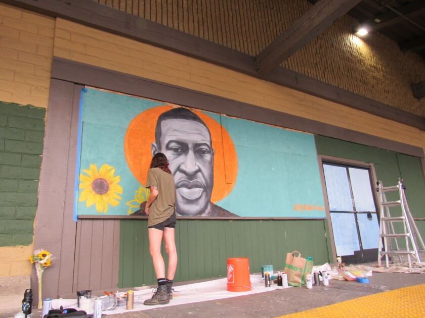 Artist Chloe Becky is shown working on a mural featuring George Floyd at the La Mesa Springs Shopping Center.