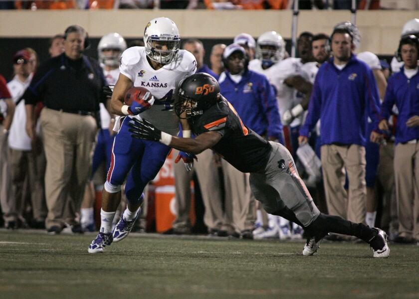 Kansas running back Connor Embree is hit by Oklahoma State safety Lyndell Johnson on Nov. 9, 2013, in Stillwater, Okla. Embree is now an assistant coach with the Kansas City Chiefs.