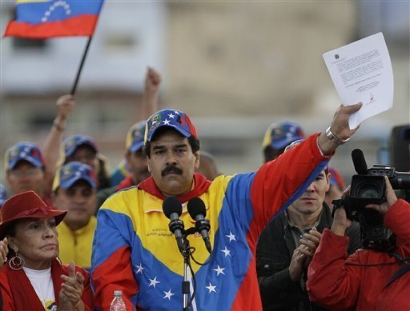 Venezuela's Vice President Nicolas Maduro holds up a letter that he said it was sent by Venezuela's President Hugo Chavez to his supporters during a demonstration commemorating the anniversary of a failed coup attempt led by Chavez in 1992, in Caracas, Venezuela, Monday, Feb. 4, 2013. The president was absent for the first time from the annual demonstrations as crowds gathered for multiple marches wearing the red T-shirts of his socialist movement. Chavez remained in Cuba, where he has been out of sight and hasn't spoken publicly since he underwent cancer surgery on Dec. 11. (AP Photo/Ariana Cubillos)