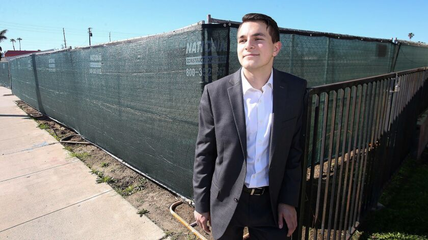 Dilan Oezkan stands next to a fence surrounding the site of the now-razed Costa Mesa Motor Inn, which provided inexpensive rooms to his family when he was a boy. Oezkan grew up homeless, moving from motel to motel with his family as a child.