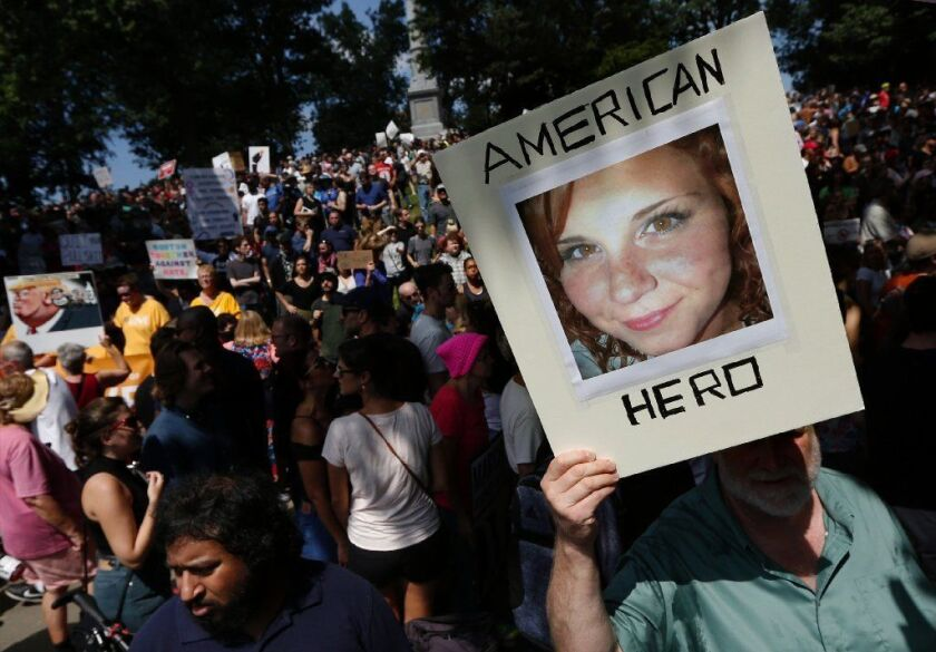 """A counter-protester holds a photo of Heather Heyer on Boston Common at a """"Free Speech"""" rally organized by conservative activists, in Boston."""