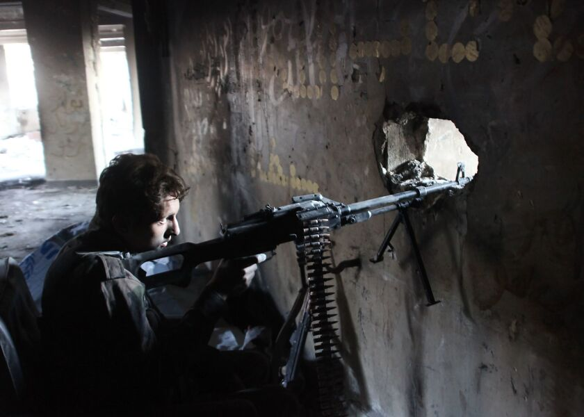 A member of Syria's pro-government forces peers through lookout in Aleppo.