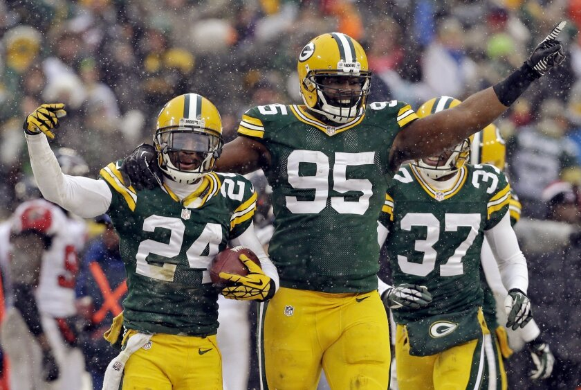 Green Bay Packers' Jarrett Bush (24) celebrates with Datone Jones (95) after Bush intercepted a pass during the final seconds of an NFL football game against the Atlanta Falcons Sunday, Dec. 8, 2013, in Green Bay, Wis. The Packers won 22-21. (AP Photo/Mike Roemer)