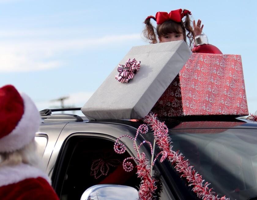 Santa Claus gets a shy wave from Brianna Johansen, 7,