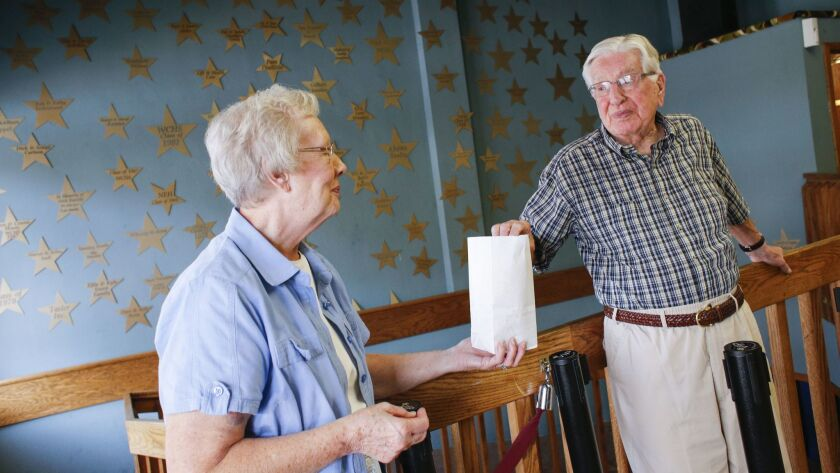 Mary and Bob Long of Webster City share a bag of popcorn in the lobby at the Webster Theater in Webs