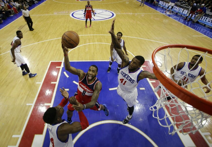 Washington Wizards' Rasual Butler (8) goes up to shoot between Philadelphia 76ers' Nerlens Noel (4) and Thomas Robinson (41) during the first half of an NBA basketball game, Friday, Feb. 27, 2015, in Philadelphia. (AP Photo/Matt Slocum)