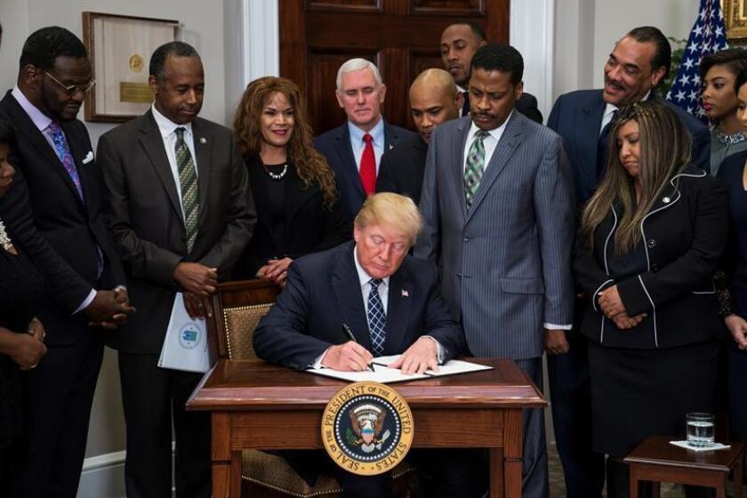 El presidente estadounidense, Donald J. Trump (c), firma junto al presidente del Centro Martin Luther King Jr., Isaac Newton Farris Jr. (3d), la proclamación del Día de Martin Luther King Jr., en la Casa Blanca de Washington, EE.UU., el 12 de enero del 2018. EFE