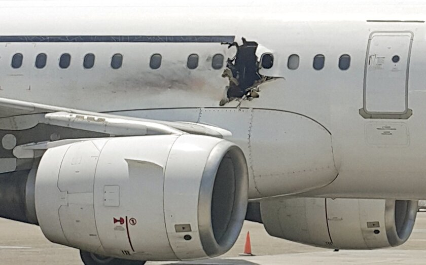 FILE - In this Tuesday, Feb. 2, 2016 file photo, a hole is photographed in a plane operated by Daallo Airlines as it sits on the runway of the airport in Mogadishu, Somalia. Abdullahi Abdisalam Borleh boarded the plane on Feb. 2 with a bomb which exploded at 11,000 feet. The blast created a hole in