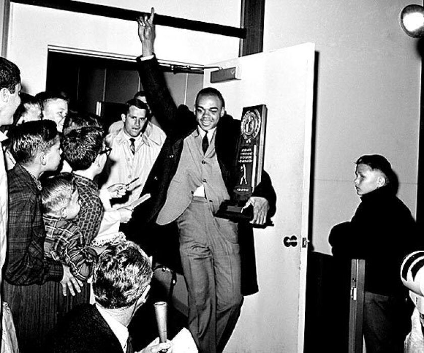 UCLA's Walt Hazzard, carries the NCAA's basketball championship trophy as the Bruins arrive in Los Angeles. More than 1,800 fans were on hand for the welcome in 1964.