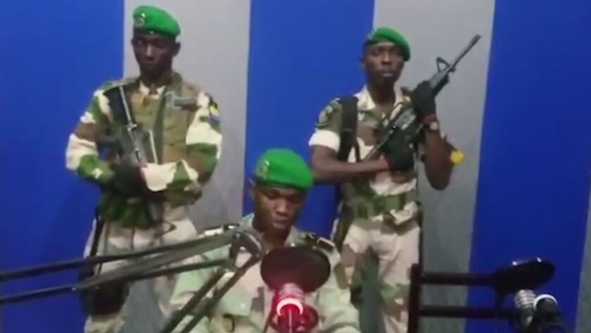 In a TV image, the self-identified commander of the Republican Guard announces the coup.