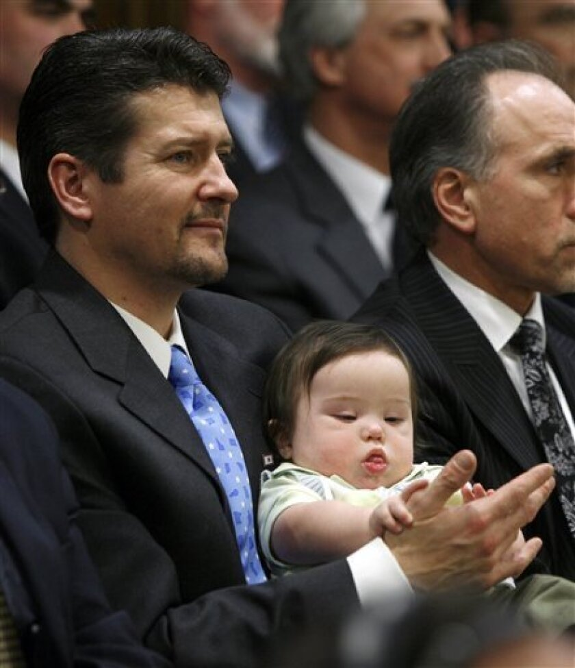 In this Jan. 22, 2009 file photo, Todd Palin , left, the husband of Alaska Gov. Sarah Palin, holds their son Trig, as Gov. Palin gives the state of the state address to a joint session of the state Senate and House in the Capitol in Juneau, Alaska. The Alaska Senate on Friday Feb. 6, 2009, found Gov. Sarah Palin's husband Todd, and nine state employees in contempt for ignoring subpoenas to testify in the Legislature's Troopergate investigation. (AP Photo/Al Grillo)