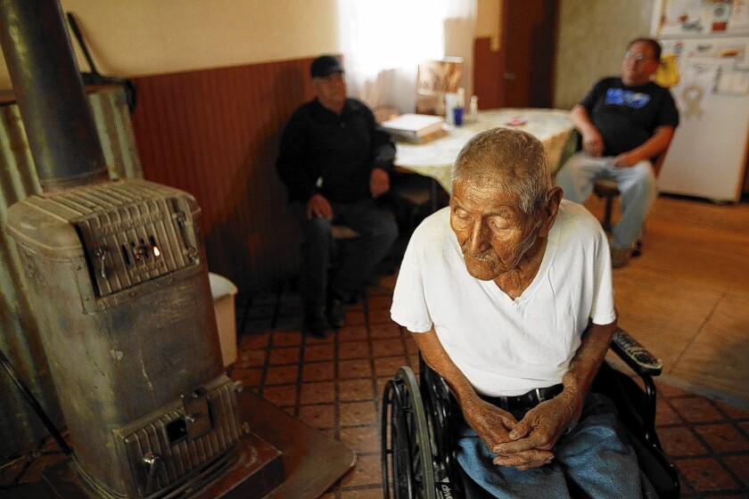 World War II veteran Tom Jones Jr., 89, a Navajo code talker, sits by the wood stove that's the only heat source in his house. The halls are too narrow to accommodate his wheelchair. Promises of housing aid to Navajo veterans have fallen short.