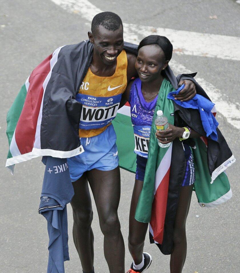 New York City Marathon winners Stanley Biwott, left, and Mary together after finishing , both from Kenya, hug at the finish line in New York, Sunday, Nov. 1, 2015. (AP Photo/Seth Wenig)