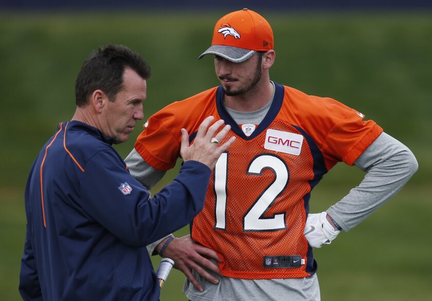 Denver Broncos head coach Gary Kubiak, left, confers with rookie quarterback Paxton Lynch during the team's NFL rookie camp football practice Friday, May 6, 2016, at the team's headquarters in Englewood, Colo. (AP Photo/David Zalubowski)